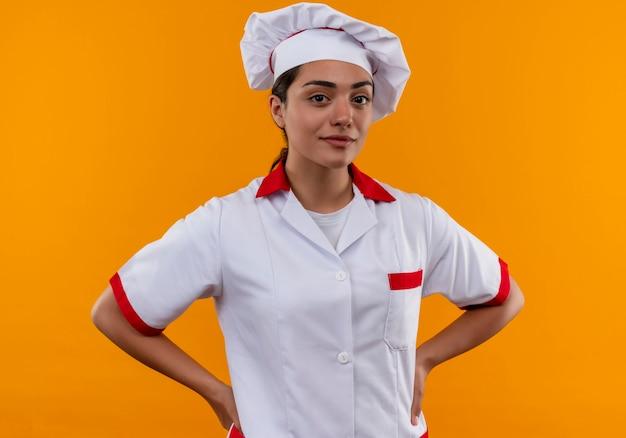Jong zelfverzekerd kaukasisch kokmeisje in uniform chef-kok legt handen op taille geïsoleerd op oranje muur met kopie ruimte