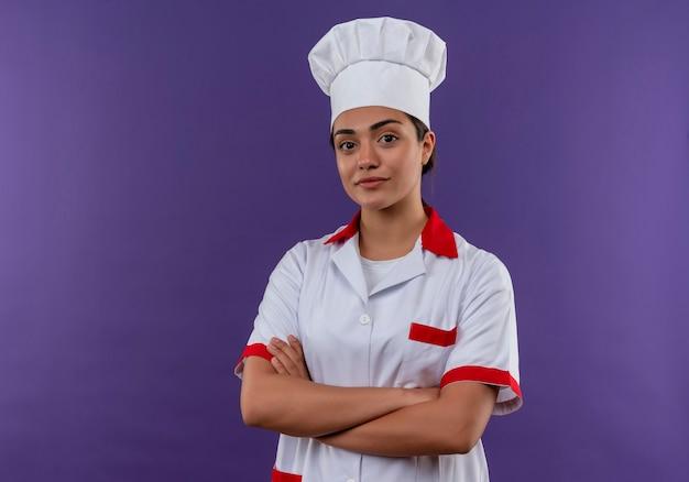 Jong zelfverzekerd kaukasisch kokmeisje in uniform van de chef-kok kruist armen en kijkt naar camera geïsoleerd op violette muur met kopie ruimte