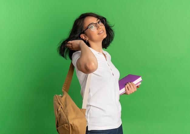 Jong zelfverzekerd vrij kaukasisch schoolmeisje met bril en rugtas staat zijwaarts legt hand op haar boeken op groen met kopie ruimte