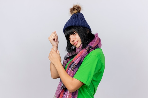 Jong ziek kaukasisch meisje dat de winterhoed en sjaal draagt die zich in profielmening bevindt die kant bekijkt die impuls controleert op pols die op witte achtergrond met exemplaarruimte wordt geïsoleerd