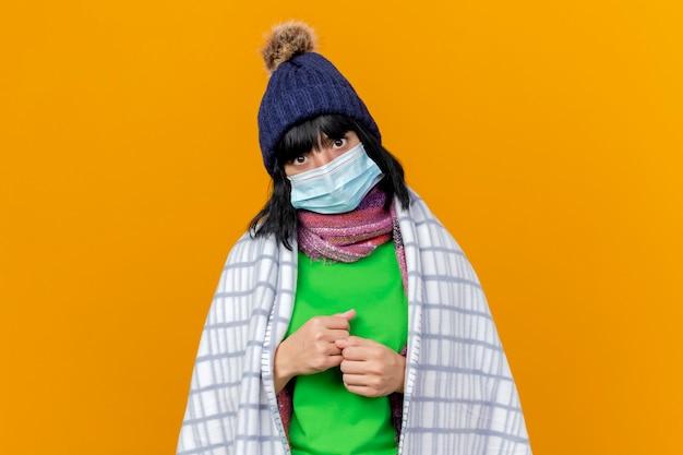 Jong ziek kaukasisch meisje dat de wintermuts en sjaal met masker draagt dat in geruite balde vuisten wordt verpakt die op oranje muur met exemplaarruimte wordt geïsoleerd