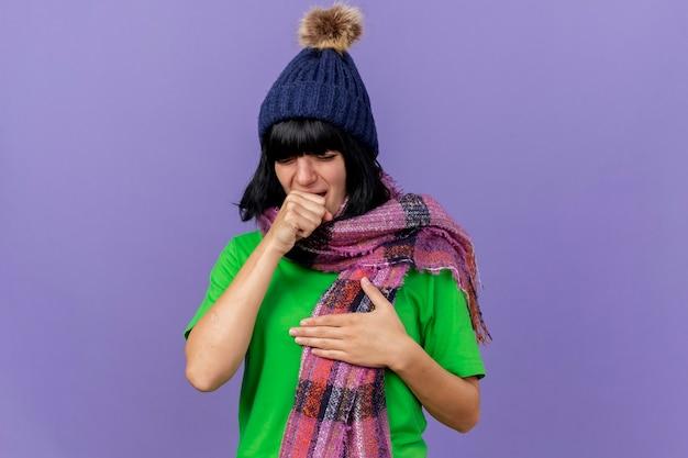Jong ziek kaukasisch meisje die de winterhoed en sjaal dragen die borst hoesten geïsoleerd op purpere achtergrond met exemplaarruimte aanraken