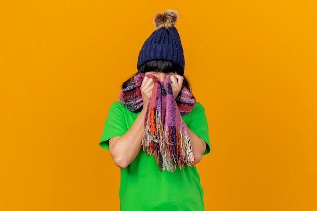 Jong ziek kaukasisch meisje die de winterhoed en sjaal dragen die de sjaal van de cameraholding op gezicht bekijken dat op oranje achtergrond met exemplaarruimte wordt geïsoleerd