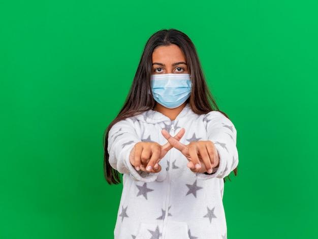 Jong ziek meisje dat camera bekijkt die medisch masker draagt dat gebaar van geen toont dat op groene achtergrond wordt geïsoleerd
