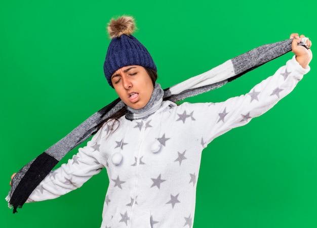 Jong ziek meisje dat de winterhoed met sjaal draagt die zelfmoordgebaar met sjaal toont die op groen wordt geïsoleerd