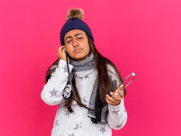 Jong ziek meisje met gesloten ogen dragen winter hoed met sjaal houden stethoscoop op oor geïsoleerd op roze
