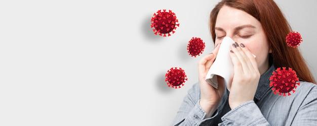 Jong ziek meisje niest in een sjaal omgeven door infectie en viruscellen op een grijze achtergrond