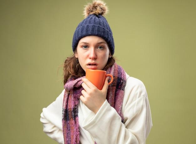 Jong ziek meisje op zoek recht vooruit dragen witte mantel en winter hoed met sjaal houden kopje thee zetten hand op heup geïsoleerd op olijfgroen