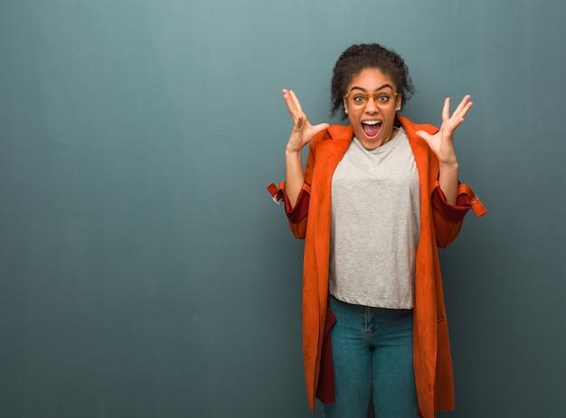 Jong zwart afrikaans amerikaans meisje dat met blauwe ogen een overwinning of een succes viert