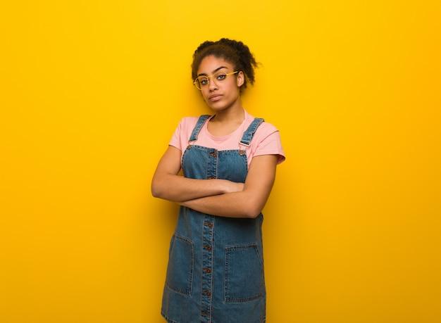 Jong zwart afrikaans amerikaans meisje dat met blauwe ogen rechtdoor kijkt