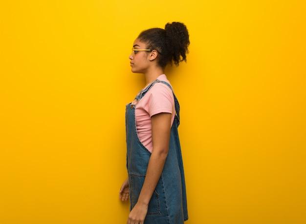 Jong zwart afrikaans amerikaans meisje met blauwe ogen aan de kant die aan voorzijde kijkt