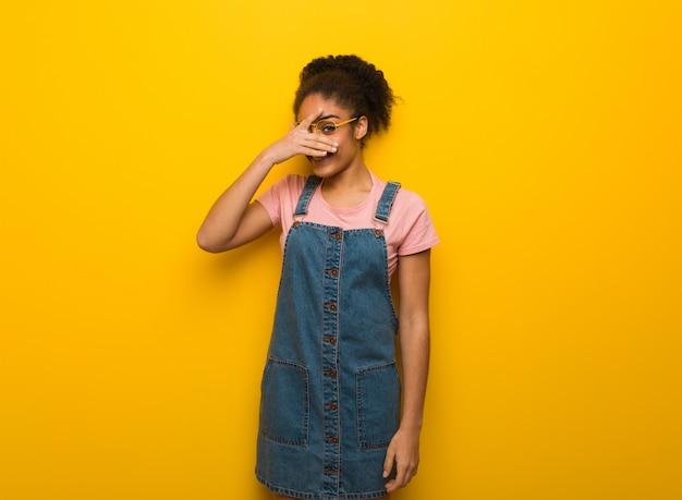 Jong zwart afrikaans amerikaans meisje met blauwe ogen beschaamd en tegelijkertijd lachend