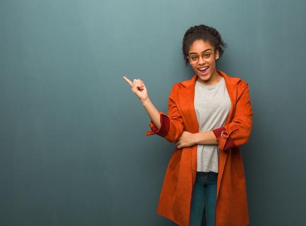 Jong zwart afrikaans amerikaans meisje met blauwe ogen die aan de kant met vinger richten