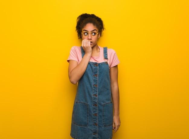 Jong zwart afrikaans amerikaans meisje met blauwe ogen die spijkers bijten, zenuwachtig en zeer angstig