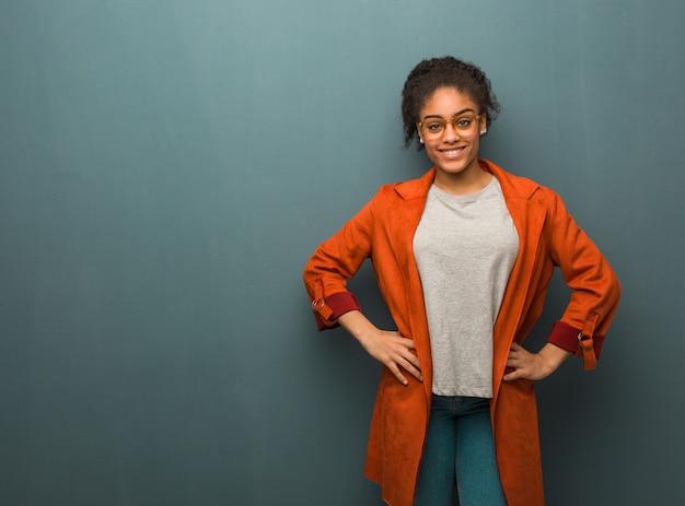 Jong zwart afrikaans amerikaans meisje met blauwe ogen met handen op heupen