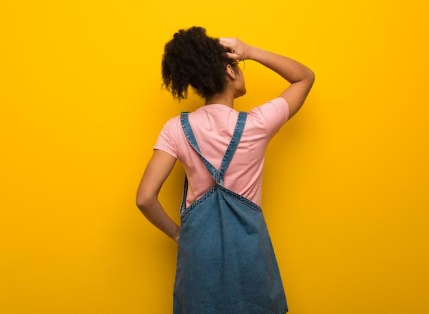 Jong zwart afrikaans amerikaans meisje met blauwe ogen van achter het denken over iets