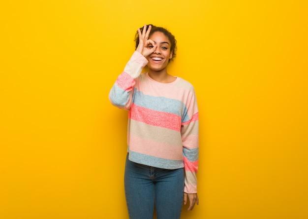 Jong zwart afrikaans amerikaans meisje met blauwe ogen zeker doend ok gebaar op oog