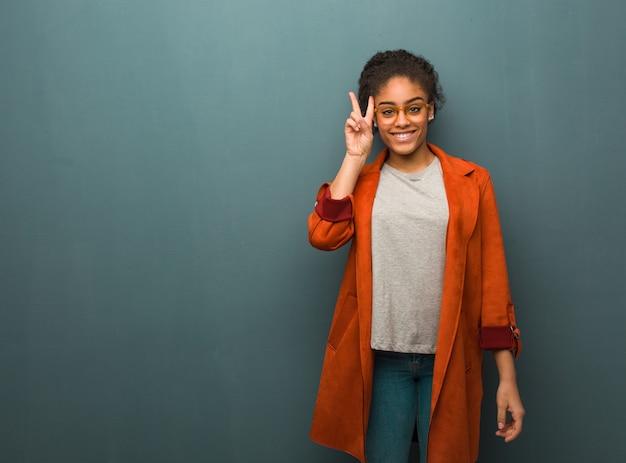 Jong zwart afrikaans amerikaans meisje met blauwe ogenpret en gelukkig het doen van een gebaar van overwinning