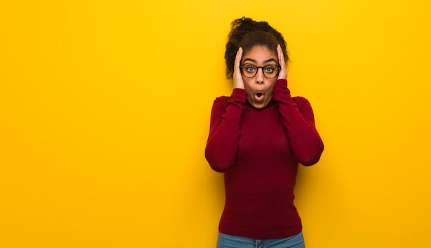Jong zwart afrikaans amerikaans meisje met blauwe verrast en geschokte ogen