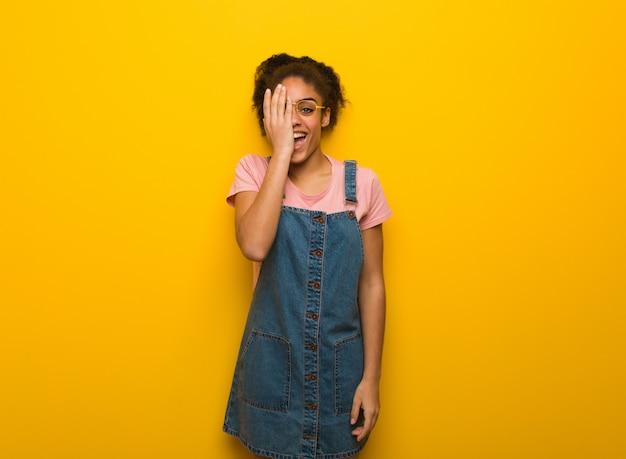 Jong zwart afrikaans amerikaans meisje met het blauwe ogen gelukkig schreeuwen en het behandelen van gezicht met hand