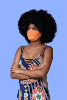 Jong zwart meisje dat gezichtsmasker draagt dat op blauwe achtergrond wordt geïsoleerd