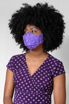 Jong zwart meisje dat gezichtsmasker draagt dat op grijze achtergrond wordt geïsoleerd