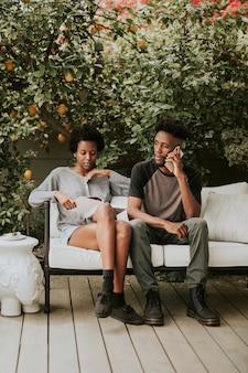 Jong zwart stel aan de telefoon in de tuin