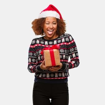 Jong zwarte die een gift in de funnny en vriendschappelijke tonende tong van kerstmis houden