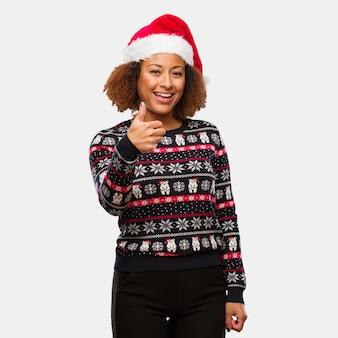 Jong zwarte in een trendy kerstmissweater met druk die en duim omhoog glimlachen opheffen