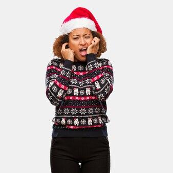 Jong zwarte in een trendy kerstmissweater met druk die oren behandelen met handen