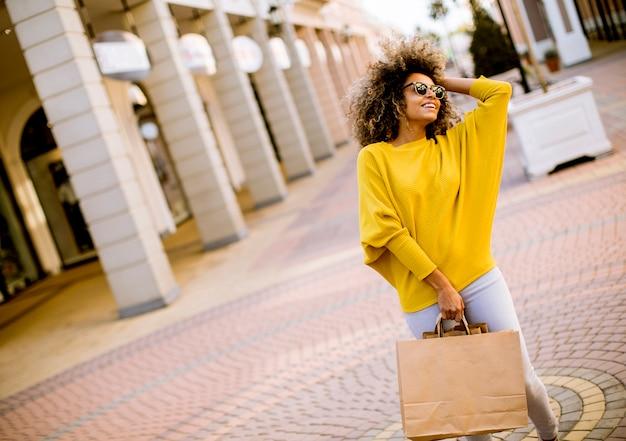 Jong zwarte met krullend haar in het winkelen