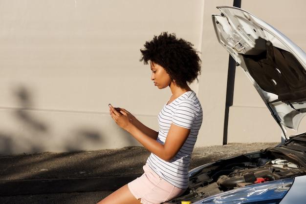 Jong zwarte status door opgesplitste auto en het gebruiken van celtelefoon voor hulp