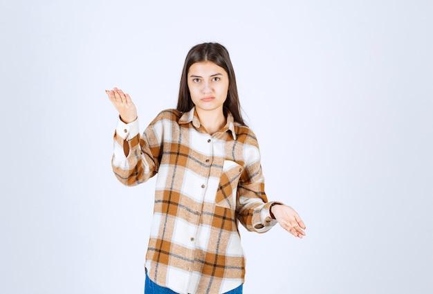 Jonge aanbiddelijke vrouw die zich op witte muur bevindt.