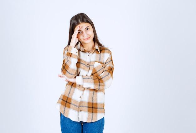 Jonge aanbiddelijke vrouw in vrijetijdskleding die zich op witte muur bevindt.