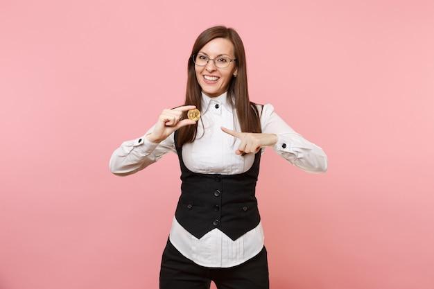 Jonge aangename succesvolle zakenvrouw in glazen wijsvinger wijzend op bitcoin geïsoleerd op pastel roze achtergrond. dame baas. prestatie carrière rijkdom concept. kopieer ruimte voor advertentie.