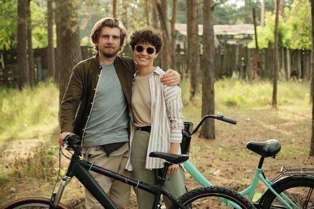Jonge aanhankelijke man die zijn gelukkige vrouw omhelst met een zonnebril terwijl ze allebei met hun fiets in een landelijke omgeving staan