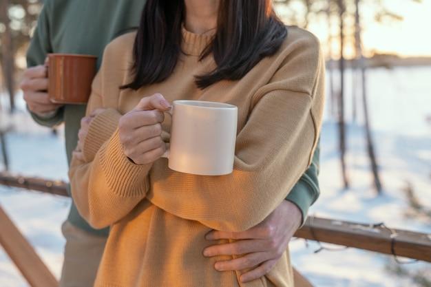 Jonge aanhankelijke man die zijn vrouw omhelst met een mok hete thee terwijl ze allebei voor de camera staan op de patio van hun landhuis