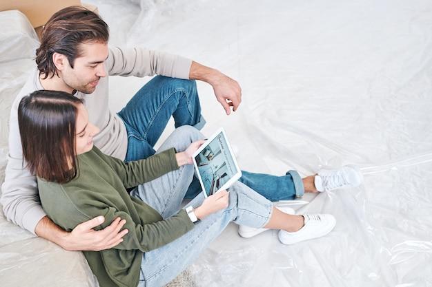 Jonge aanhankelijke man en vrouw die met touchpad online ideeën van nieuwe vlakke planning door bank bekijken