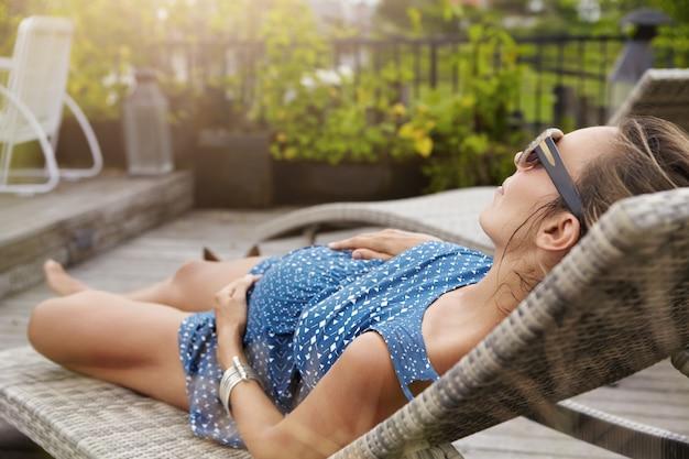 Jonge aanstaande moeder die een zonnebril en zomerjurk draagt die slaapt of een dutje doet op een ligstoel, de handen op haar buik houdt.