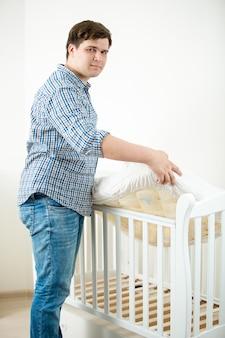 Jonge aanstaande vader die matras in babybedje legt op kinderdagverblijf