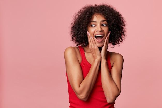 Jonge aantrekkelijke afrikaanse amerikaan met een afro-kapsel met verrukking kijkt links naar de lege ruimte, haar handen raken haar gezicht, voelt zich tevreden, kijkt verrast, geïsoleerd