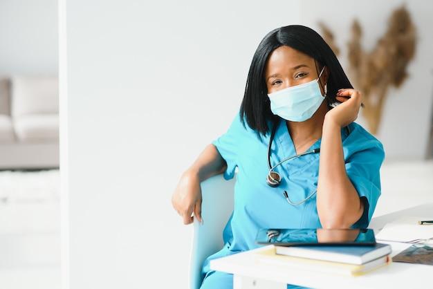 Jonge aantrekkelijke afrikaanse arts met gezichtsmasker
