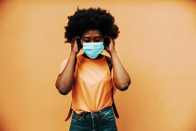 Jonge aantrekkelijke afrikaanse vrouw met krullend haar die gezichtsmasker opzet om verspreiding van coronavirus / covid 19 te voorkomen.
