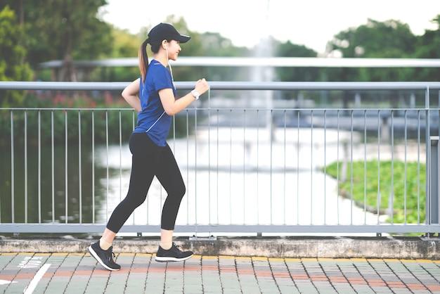 Jonge aantrekkelijke aziatische agentvrouw die bij stoepmanier loopt