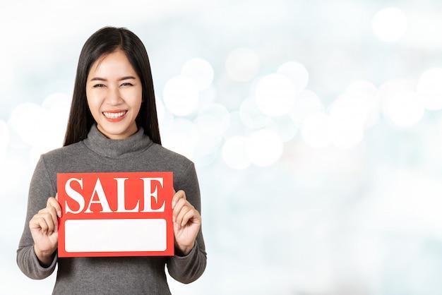 Jonge aantrekkelijke aziatische het verkoopuithangbordkaart die van de vrouwenholding voor prijskaartje tonen