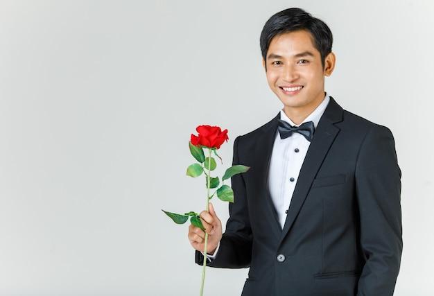 Jonge aantrekkelijke aziatische man, binnenkort bruidegom in zwarte smoking die lacht en roos vasthoudt. concept voor pre-huwelijksfotografie.
