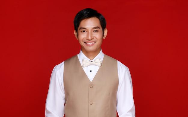 Jonge aantrekkelijke aziatische man die binnenkort een bruidegom wordt met een wit overhemd en een beige vest tegen een rode achtergrond. concept voor pre-huwelijksfotografie.