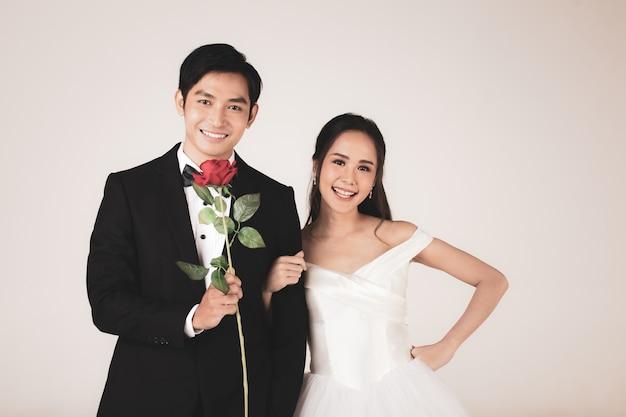Jonge aantrekkelijke aziatische paar, binnenkort bruid en bruidegom, vrouw die witte trouwjurk draagt. man met zwarte smoking die roos vasthoudt en samen staat. concept voor pre-huwelijksfotografie.