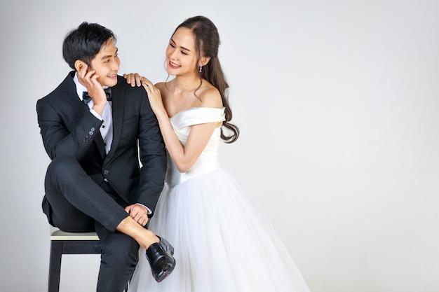 Jonge aantrekkelijke aziatische paar, binnenkort bruid en bruidegom, vrouw die witte trouwjurk draagt. man met zwarte smoking, samen zitten. concept voor pre-huwelijksfotografie.