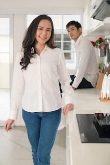 Jonge aantrekkelijke aziatische paar met vrouw op de voorgrond en man zittend op de achtergrond in witte keuken met bord op tafel. concept voor gezonde en gelukkige liefde en koken.